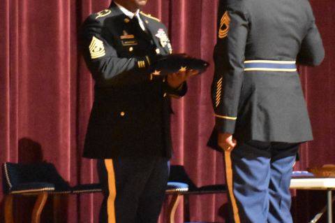 Ret. Command Sergeant Major Gregory Jackson receives U.S. flag during retirement ceremony from Master Sergeant David Brooks who served as soldier under Jackson 17 years ago.