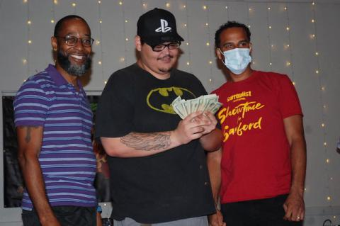 Priceless Hero poses for photos with his winnings and host Jay Love, left, and show organizer Lawrence Gordon, right.